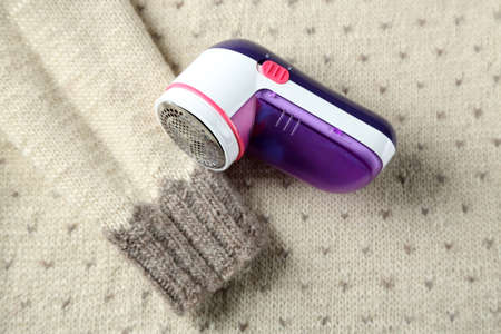 unsightly: Wool shaver on wool sweater background Stock Photo