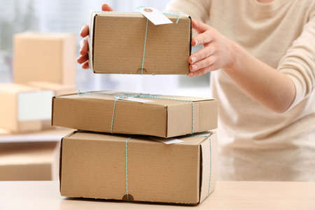 Woman gives parcel in post office Stock Photo