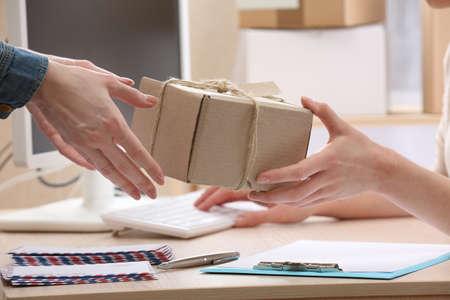 Žena dává balíček v poště
