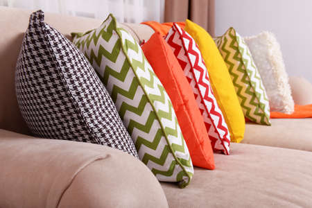 window curtains: Sofa with colorful pillows in room