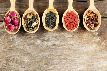 wooden spoon: Collection of tea and natural additives in wooden spoons, on old wooden table