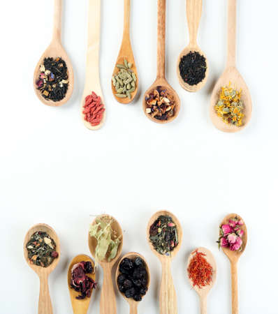 additives: Collection of tea and natural additives in wooden spoons, isolated on white