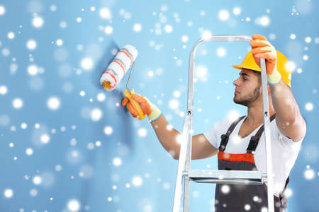 Young worker renewing apartment over snow effect