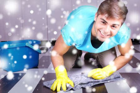 Young man cleaning floor in room over snow effect Stock Photo