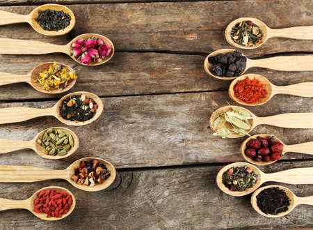 tea ceremony: Collection of tea and natural additives in wooden spoons, on old wooden table