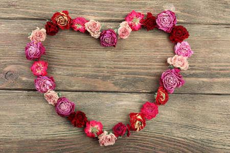 flores secas: flores secas en forma de corazón en el fondo de madera