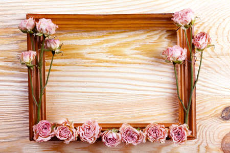 rose photo: Photo frame with dried flowers on wooden background