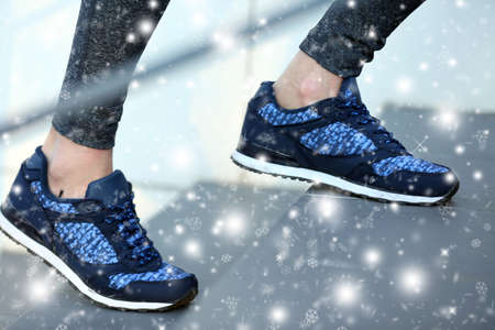 sneakers: Sports woman legs in sneakers on stairs over snow effect Stock Photo