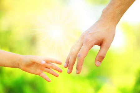 Hände von Vater und Sohn halten einander