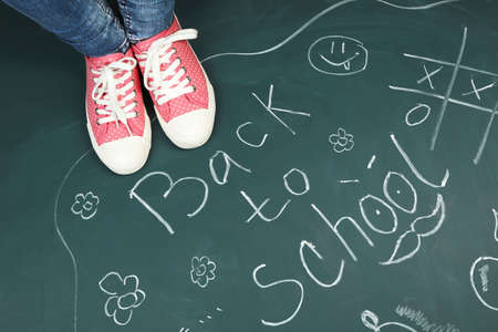 inscriptions: Female feet on blackboard background with inscriptions and sketches Stock Photo