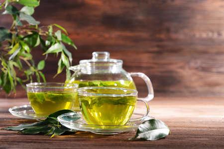 menta: Tazas de té verde en la mesa sobre fondo de madera