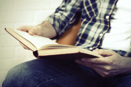 cramming: Young man reading book, close-up, on light background