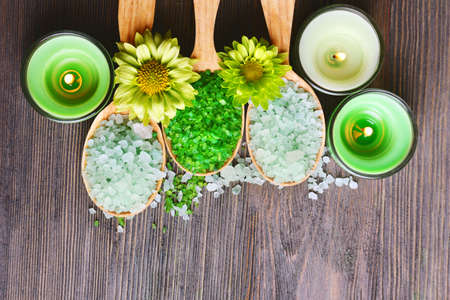 wooden color: Beautiful composition with sea salt in wooden spoons and flowers on table close up