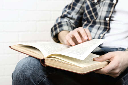 memoirs: Young man reading book, close-up, on light background