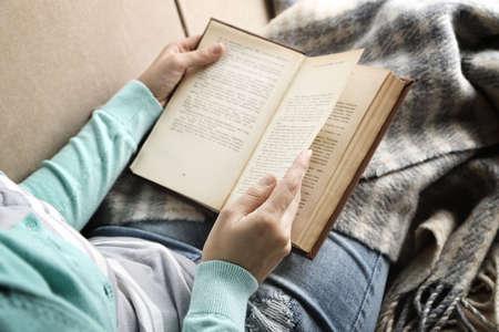 Mladá žena čtení knihy, close-up, na domácí interiéru pozadí Reklamní fotografie
