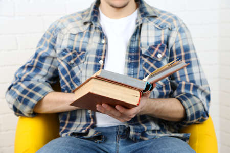 bibliophile: Young man reading book, close-up, on light background