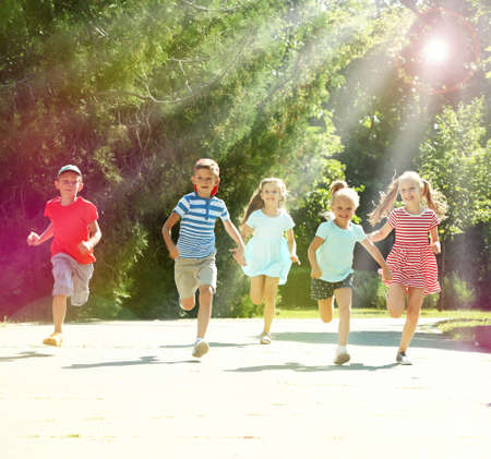 sol radiante: niños activos felices que se ejecutan en el parque Foto de archivo