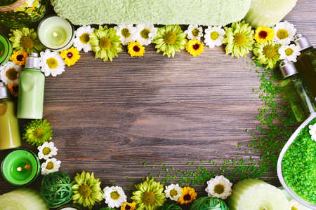 Beautiful spa composition with flowers as frame on wooden background