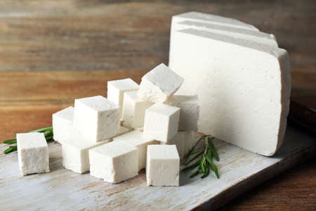 Sliced feta cheese with rosemary on table on wooden background Standard-Bild