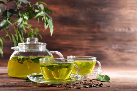 Kopjes groene thee op tafel op houten achtergrond
