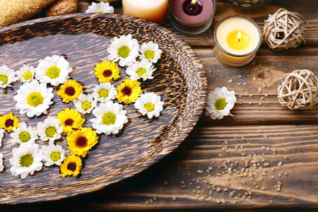 skin care products: Candles with flowers on plate on table close up
