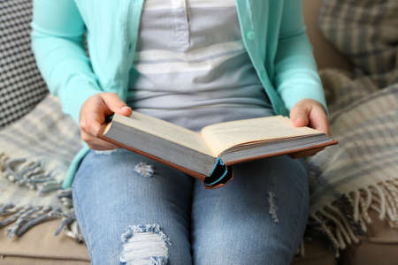 cramming: Young woman reading book, close-up, on home interior background