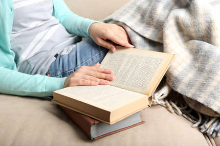 bibliophile: Young woman reading book, close-up, on home interior background