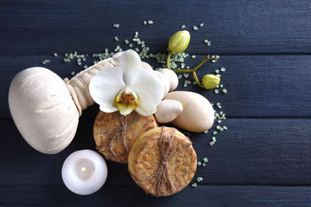 spa flower: Still life with beautiful blooming orchid flower, spa treatment and pebbles, on wooden background