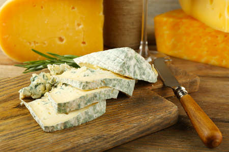 chees: Slices of tasty blue cheese on cutting board close up