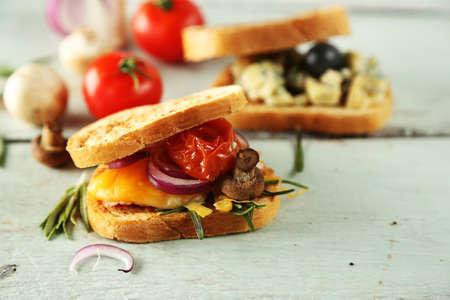 bocadillo: Sabrosos sandwiches en mesa de madera, de cerca Foto de archivo