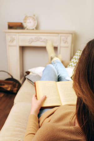 living wisdom: Woman reading book on sofa in room Stock Photo