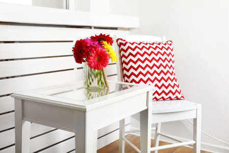 white pillow: Modern interior with white chair and pillow near coffee table with colorful gerbera