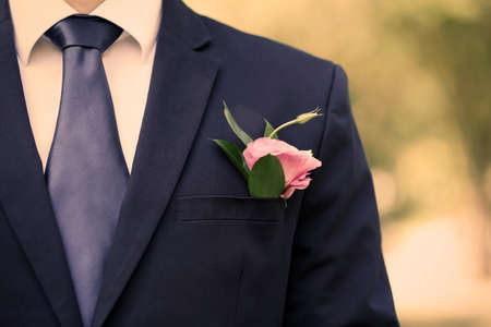 boutonniere: Groom with boutonniere outdoors
