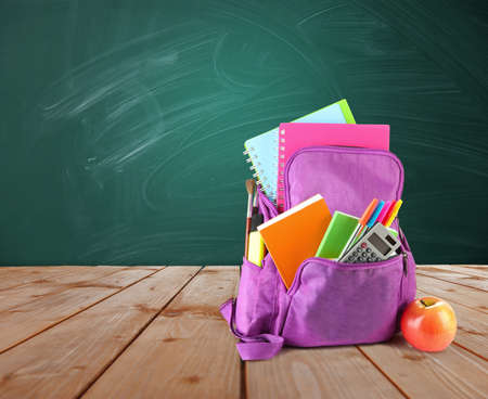 vibrant colors: Backpack with school supplies on wooden table on green desk background