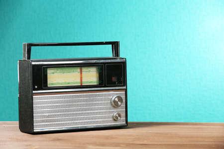 radio station: Old retro radio on table on green wall background