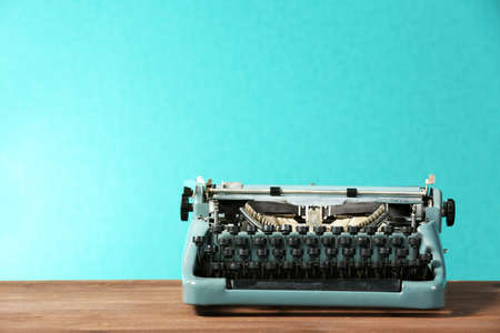 Old retro typewriter on table on green background 스톡 콘텐츠