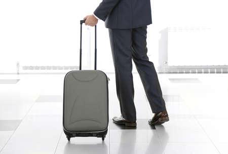 maleta: Hombre que sostiene la maleta sobre fondo claro Foto de archivo