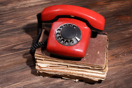 red telephone: Retro red telephone on table close-up Stock Photo