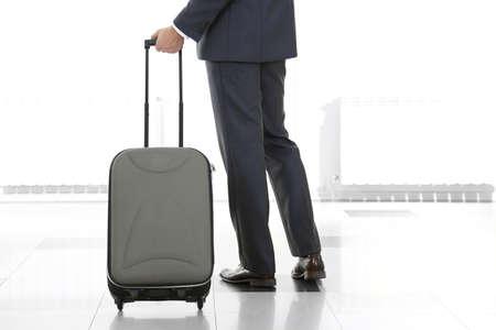 maletas de viaje: Hombre que sostiene la maleta sobre fondo claro Foto de archivo