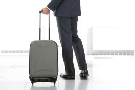Man holding suitcase on light background