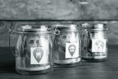 cash money: Los rollos de billetes de d�lar para distintas necesidades en frascos de vidrio de mesa de madera Foto de archivo