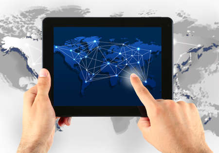 Close up of human hand touching screen of tablet pc with world map and network