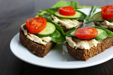 the greens: Delicious sandwiches with vegetables and greens on plate close up Stock Photo