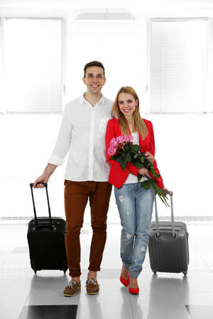 Portrait of young happy couple with baggage in airport Imagens