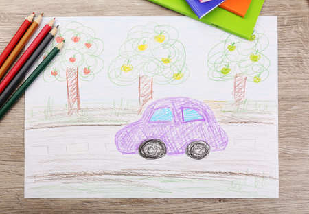 drawing paper: Kids drawing on white sheet of paper with crayons, closeup Stock Photo