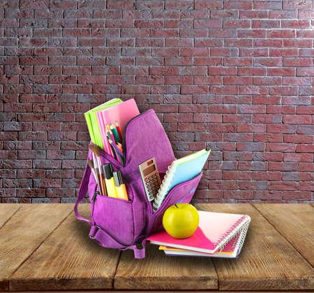 briks: School backpack on wooden desk, on bricks wall background
