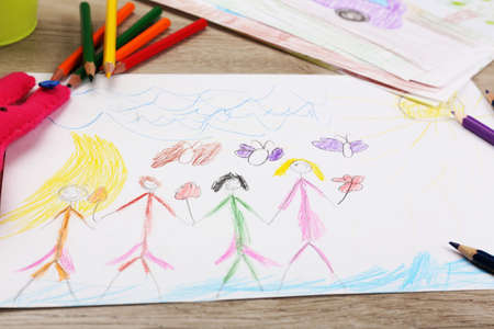 kid drawing: Kids drawing on white sheet of paper with crayon,closeup Stock Photo