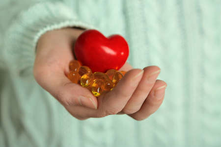 holding close: Hand holding red heart and cod liver oil, close up