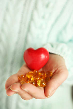 cod oil: Hand holding red heart and cod liver oil, close up
