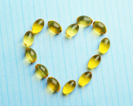 cod oil: Heart of cod liver oil, on blue background Stock Photo